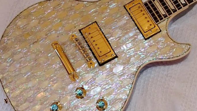 A vintage Gibson Les Paul Deluxe gets a 24 carat gold and mother of pearl makeover